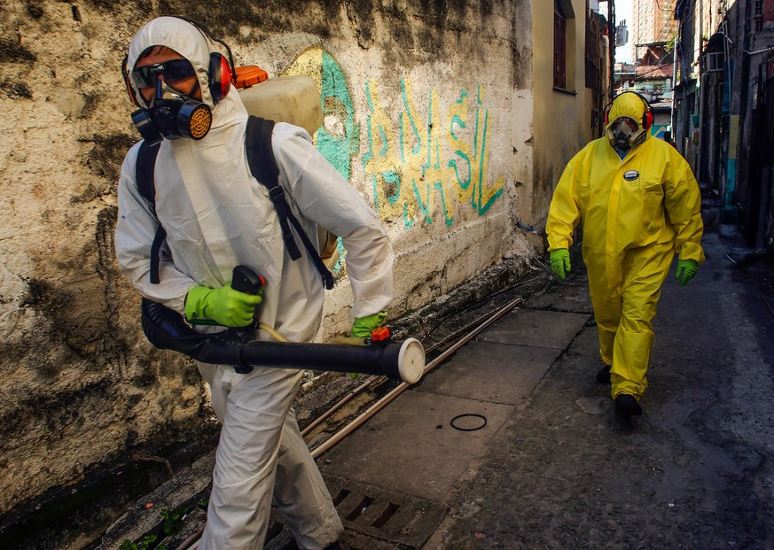 NITEROI, BRAZIL - MARCH 25: Agents of the sanitary department clean streets and alleys of the Vila Ipiranga Favela, in Fonseca neighborhood on March 25, 2020 in Niteroi, Brazil. Vila Ipiranga is the first community (Favela) in the country to receive the visit of sanitary agents using the same technology applied in China to help prevent the spreading of the coronavirus (COVID-19). According to the Ministry of health, as of today, Brazil has 2271 confirmed cases infected with the coronavirus (COVID-19) and at least 47 recorded deceases. (Photo by Luis Alvarenga/Getty Images)