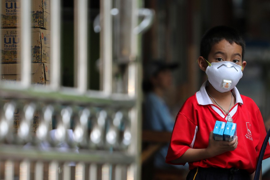 A student wears a mask as he waits to be picked up, as classes in over 400 Bangkok schools have been cancelled due to worsening air pollution, at a public school in Bangkok, Thailand, January 30, 2019. REUTERS/Athit Perawongmetha