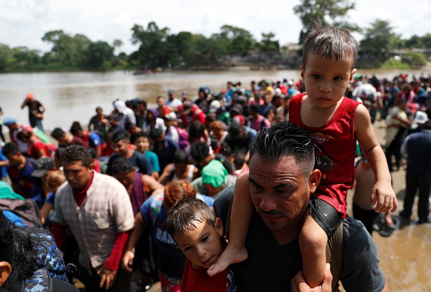 Migrants, part of a caravan traveling to the U.S., stand in line to climb a little hill after crossing the Suchiate river, a natural border between Guatemala and Mexico, in Ciudad Hidalgo, Mexico October 29, 2018. REUTERS/Carlos Garcia Rawlins
