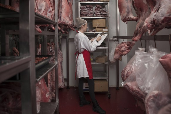 Woman with clipboard in butchery cold store model released Symbolfoto property released PUBLICATIONxINxGERxSUIxAUTxHUNxONLY ZEF010340