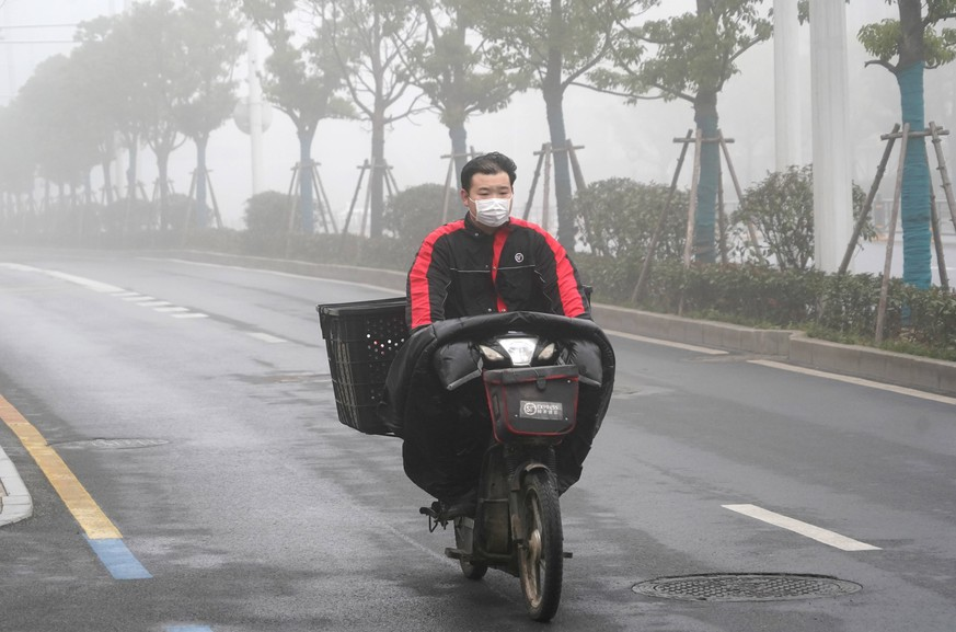 200223 -- WUHAN, Feb. 23, 2020 -- A delivery man is seen working amid fog in Wuhan, central China s Hubei Province, Feb. 22, 2020.  Xinhua Headlines: Under the masked sky: Wuhan makes lockdown sacrifice ChengxMin PUBLICATIONxNOTxINxCHN