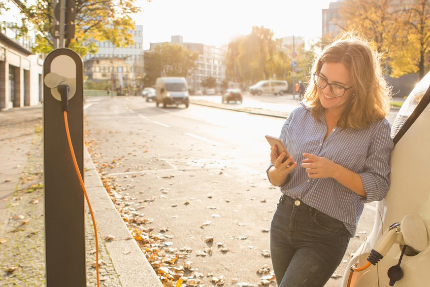 Young woman is standing near the electric car and holding smartphone. The rental car is charging at the charging station for electric vehicles. Car sharing.