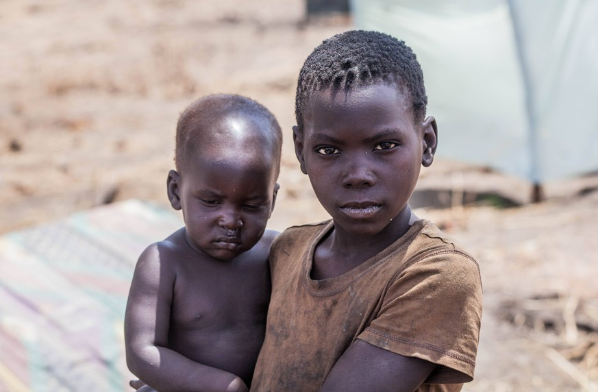 Mass exodus in Central Equatoria - 10/02/2017 - Uganda - A young boy carries his brother in the Palorinya settlement, Moyo district, northern Uganda. Most refugees (86%) fleeing South Sudan are women and children, including survivors of violent attacks and sexual assault, and children that have been separated from their parents, travelled alone or have become primary caregivers to younger siblings. - PUBLICATIONxINxGERxSUIxAUTxONLY NataliaxJidovanux/xLexPictorium LePictorium_0153920