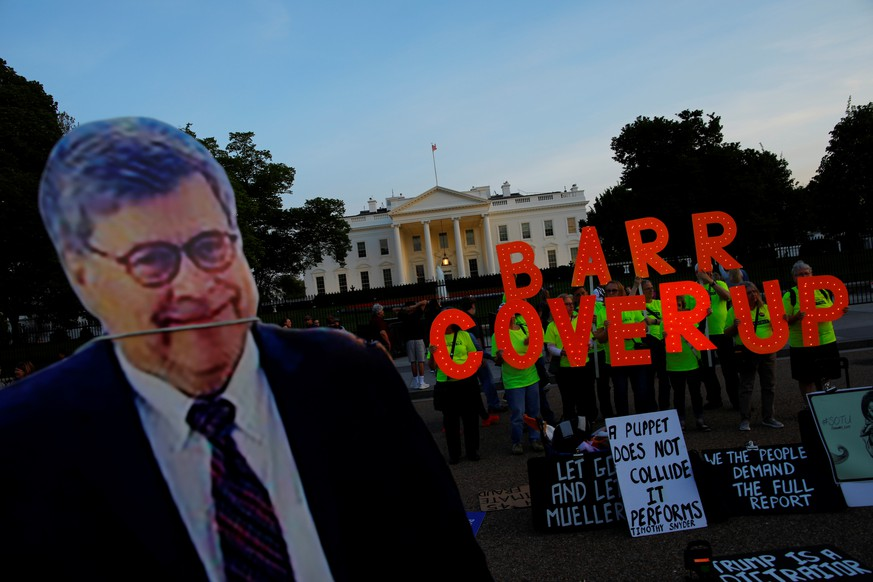 A cardboard cutout of U.S. Attorney General William Barr is seen as protesters hold signs which read