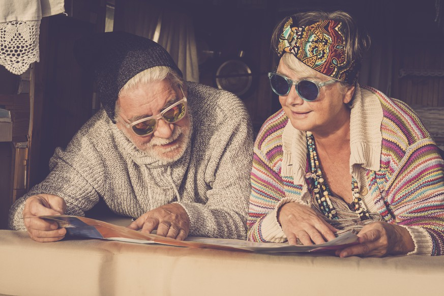 Adults mature couple of caucasian people hippy style planning on the map the next step of van life vacation - cheerful happy man and woman retired and living a new life - colors and enjoying