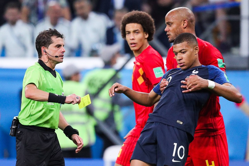 ST PETERSBURG, RUSSIA - JULY 10, 2018: Referee Andres Cunha (L) shows a yellow card to France s Kylian Mbappe (R front) in the 2018 FIFA World Cup WM Weltmeisterschaft Fussball Semi-final match between France and Belgium at Saint Petersburg Stadium. Also pictured: Belgium s Axel Witsel and Vincent Kompany (L-R background). Sergei Bobylev/TASS PUBLICATIONxINxGERxAUTxONLY TS088E77