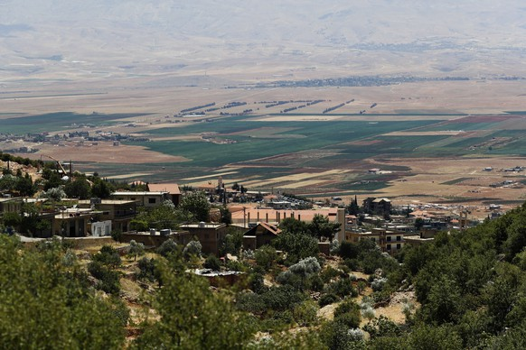 In this Monday, July 23, 2018, photo, a general views shows a part of the Bekaa valley from the village of Deir al Ahmar, 12 kilometers (about 7 miles) northwest of the town of Baalbek in the Bekaa Valley, Lebanon. In the fields of this quiet village surrounded by mountains, men and women work on removing dirt and dry leaves around cannabis plants from which many people in this eastern region make a living. (AP Photo/Hassan Ammar)
