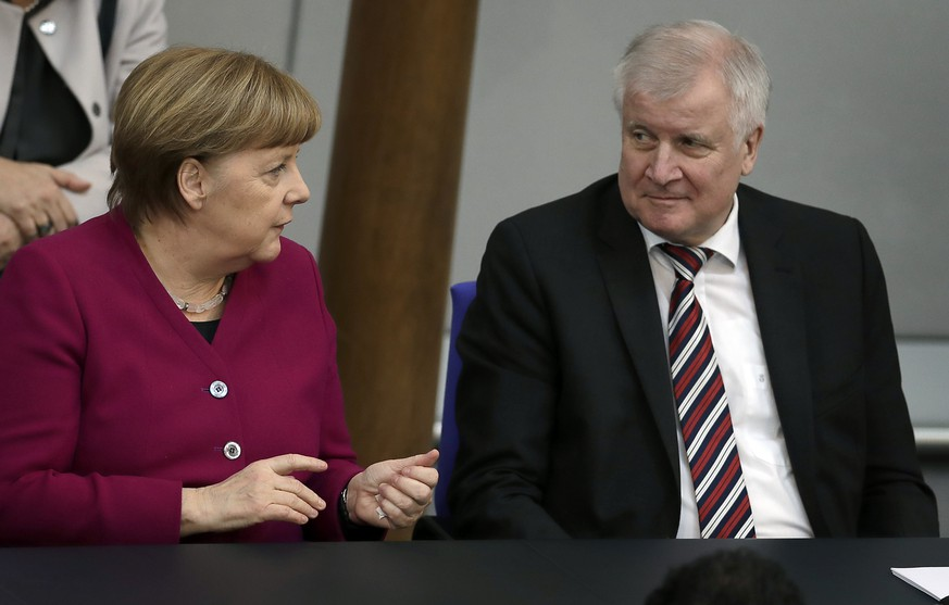 German Chancellor Angela Merkel, left, and German Interior Minister Horst Seehofer, right, talk during a meeting of the German federal parliament, Bundestag, at the Reichstag building in Berlin, Germany, Wednesday, March 21, 2018. (AP Photo/Michael Sohn) |