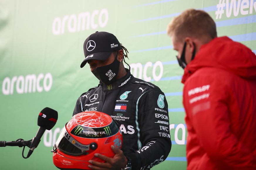 Mercedes driver Lewis Hamilton, left, of Britain receives a helmet of former German driver Michael Schumacher from Mick Schumacher, right, after he wins the Eifel Formula One Grand Prix at the Nuerburgring racetrack in Nuerburg, Germany, Sunday, Oct. 11, 2020. Hamilton gets the helmet as a gift from Michael Schumacher's son Mick because he equals Schumacher's record of 91 wins in the Formula One. (Bryn Lennon, Pool via AP)