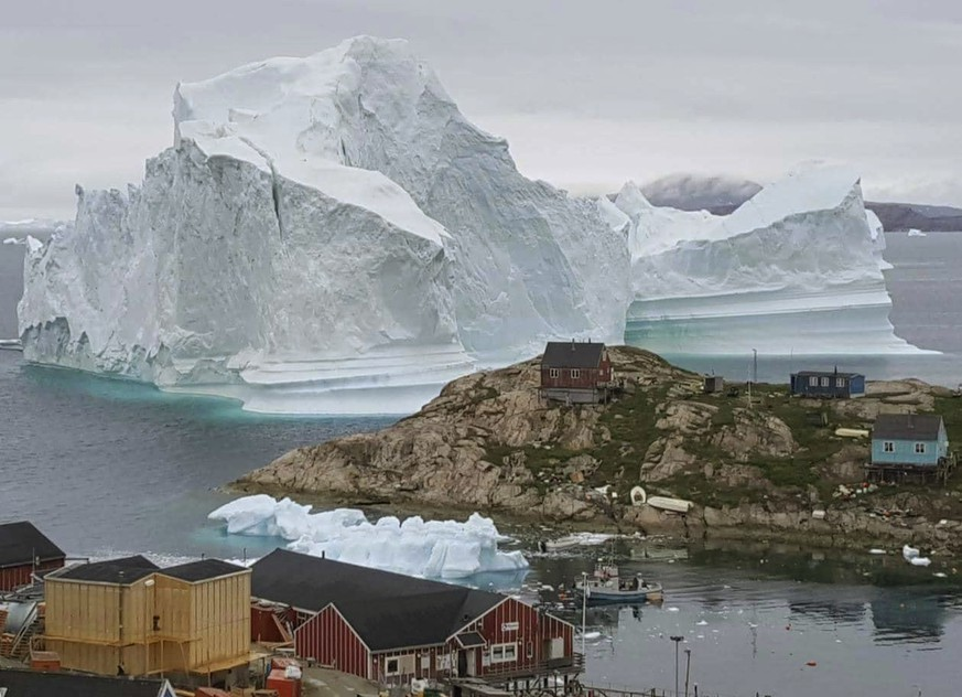 In this Thursday, July 12, 2018 photo, a view of an Iceberg, near the village Innarsuit, on the northwestern Greenlandic coast. Scientists have watched an iceberg four miles long break off from a glacier. The iceberg is allegedly grounded on the sea floor. Residents in houses near the shore are prepared for an evacuation. (Karl Petersen/Ritzau Scanpix via AP)