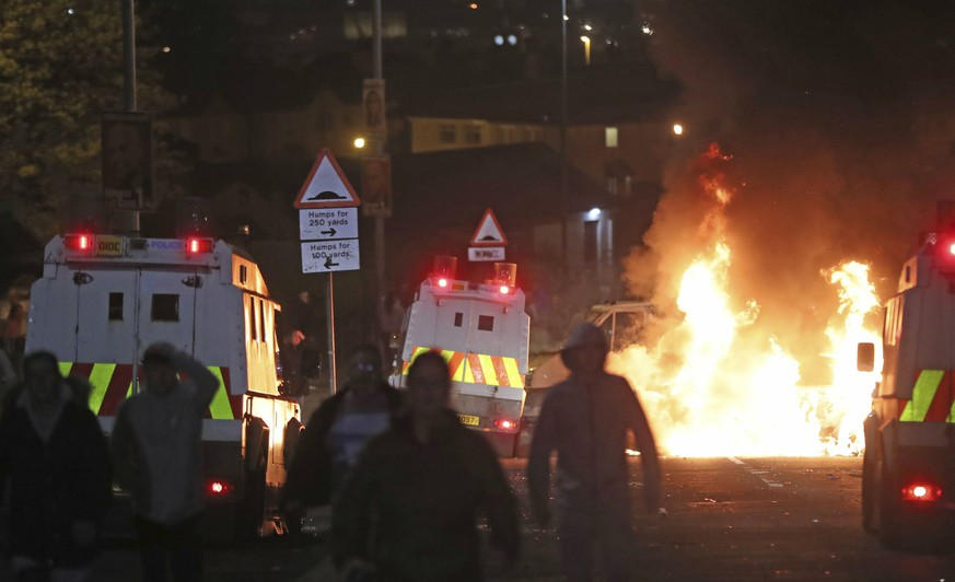 A car burns after petrol bombs were thrown at police in Creggan, Londonderry, in Northern Ireland, Thursday, April 18, 2019. (Niall Carson/PA via AP)