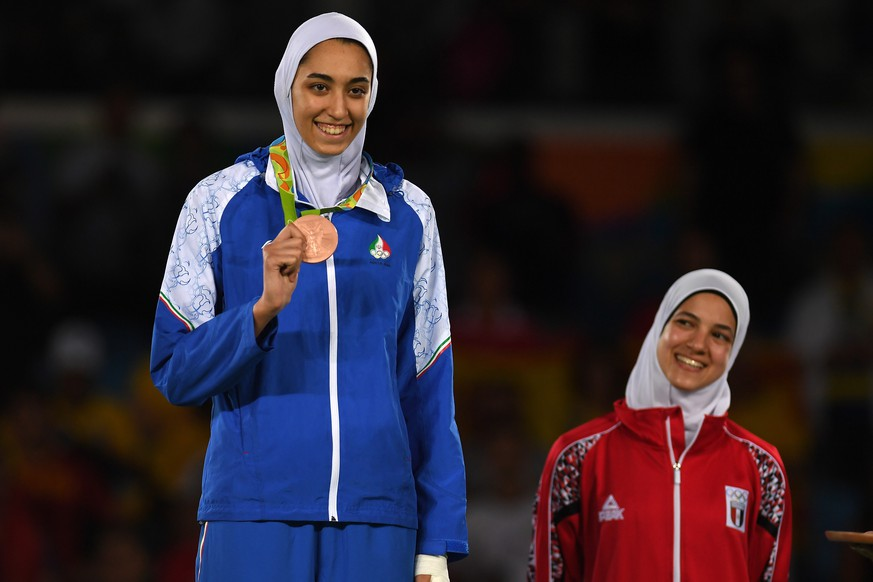 RIO DE JANEIRO, BRAZIL - AUGUST 18:  Bronze medalists, Kimia Alizadeh Zenoorin of the Islamic Republic of Iran and Hedaya Wahba of Egypt celebrate on the podium after the Women's -57kg Bronze Medal Taekwondo contest at the Carioca Arena on Day 13 of the 2016 Rio Olympic Games on August 18, 2016 in Rio de Janeiro, Brazil.  (Photo by Laurence Griffiths/Getty Images)