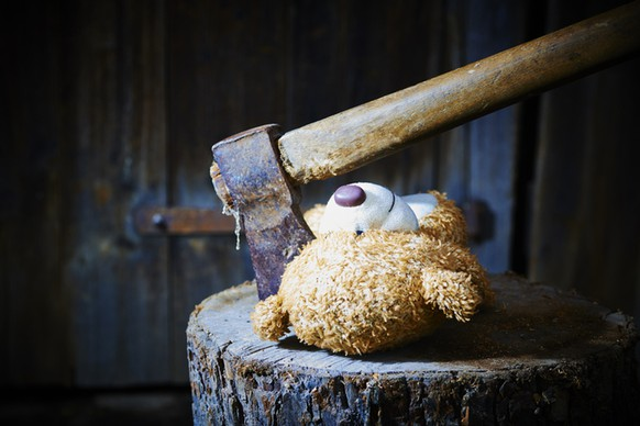 Toy teddy bear lying on a wooden log killed by an ax