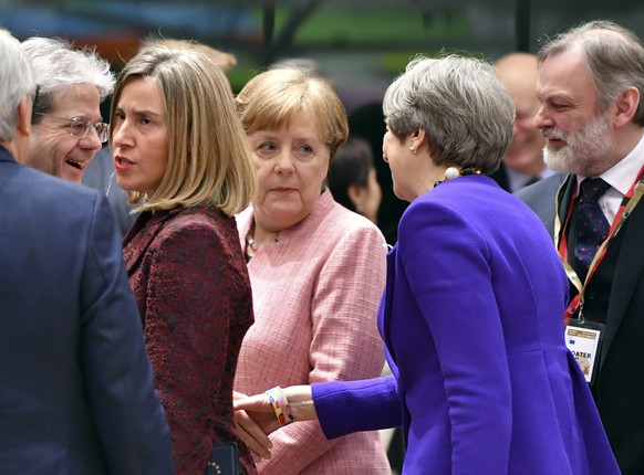 British Prime Minister Theresa May, third right, reaches out to shake hands with Italian Prime Minister Paolo Gentiloni, second left, during a round table meeting at an EU summit at the Europa building in Brussels on Thursday, March 22, 2018. Leaders from the 28 European Union nations meet for a two-day summit to assess the state of Brexit negotiations, the prospect of a trade war with the United States and how to react to Russia following to the nerve agent attack in Britain. German Chancellor Angela Merkel is at center. (AP Photo/Geert Vanden Wijngaert)