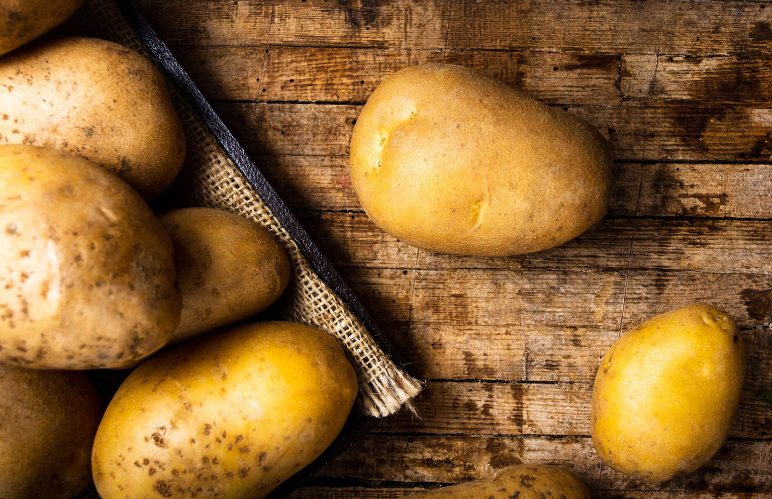 Potatoes on a rustic wooden background closeup