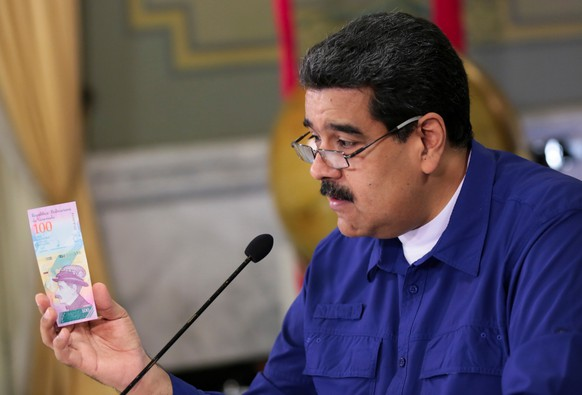 Venezuela's President Nicolas Maduro holds a bank note of the new Venezuela's currency Bolivar Soberano (Sovereign Bolivar) as he speaks during a meeting with ministers at Miraflores Palace in Caracas, Venezuela July 25, 2018. Miraflores Palace/Handout via REUTERS ATTENTION EDITORS - THIS PICTURE WAS PROVIDED BY A THIRD PARTY.