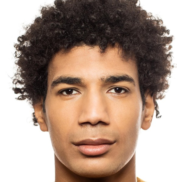 Portrait of young male against white background. Serious man is wearing yellow casuals. He is having short curly hair.