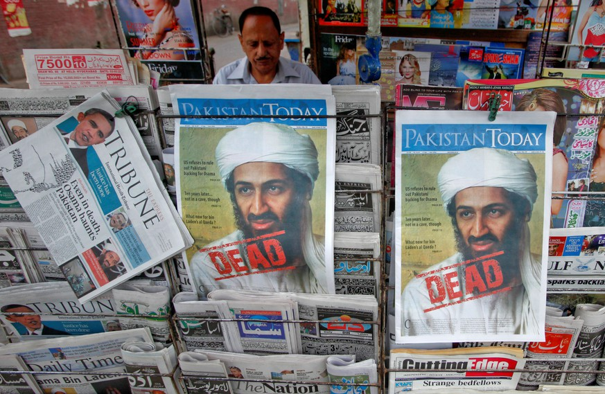 FILE PHOTO: A roadside vendor sells newspapers with headlines about the death of al Qaeda leader Osama bin Laden, in Lahore May 3, 2011.  REUTERS/Mohsin Raza/File Photo