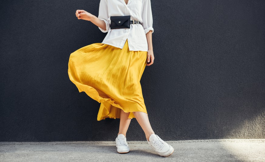 Horizontal cropped image of stylish slim woman in beautiful yellow skirt. Caucasian female fashion model standing over gray wall background outdoor with copy space.