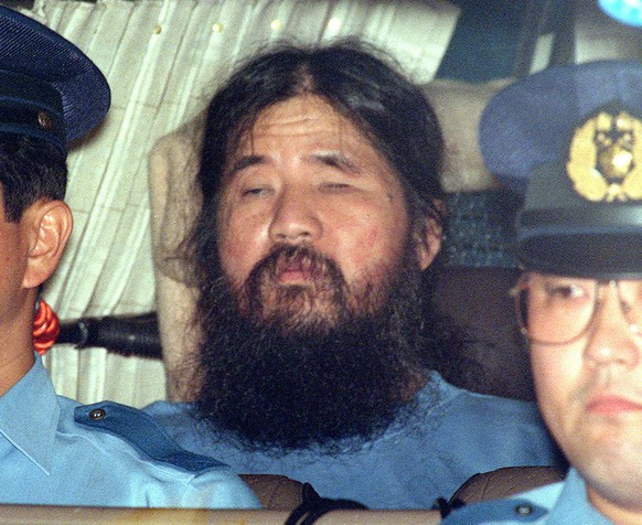 FILE - In this Sept. 25, 1995, file photo, cult leader Shoko Asahara, center, sits in a police van following an interrogation in Tokyo. Thirteen Japanese cult members may be sent to the gallows any day now for a deadly 1995 gas attack on the Tokyo subway system and other crimes. Or they might not. Such is the secrecy that surrounds Japan's death penalty system. Tuesday, March 20, 2018, marks 23 years since members of the Aum Shinrikyo cult punctured plastic bags to release sarin nerve gas inside subway cars, sickening thousands and killing 13. Cult leader Shoko Asahara and a dozen followers have been sentenced to death for that and other crimes that killed 27 in all. (Kyodo News via AP, File)