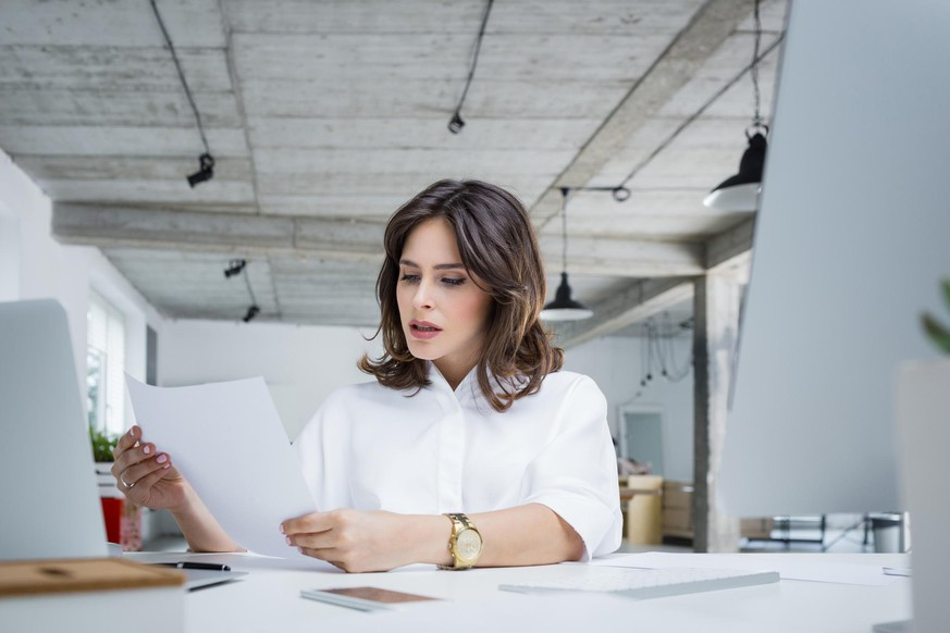 Worried businesswoman reading a document while sitting at her desk in office. Female executive reading a paper seriously.