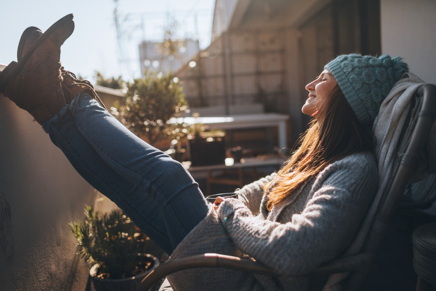 Photo of a young woman taking a few minutes off to relax on the balcony over the city, on a beautiful, sunny, autumn day