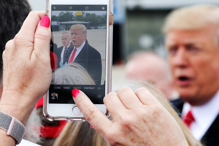 A woman in the crowd on the airport tarmac shoots a mobile phone picture of U.S. President Donald Trump at Cincinnati Municipal Lunken Airport as he arrives for an evening campaign rally in Cincinnati, Ohio, U.S., October 12, 2018. REUTERS/Jonathan Ernst