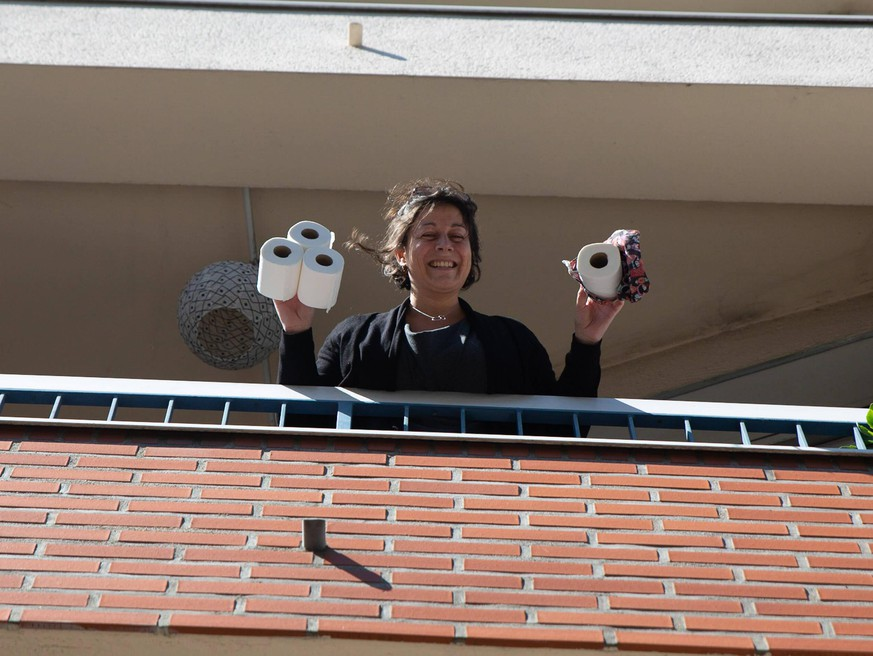 FRANCE - HEALTH - CORONAVIRUS PANDEMIC ILLUSTRATION A woman standing on a balcony smiles while holding several rolls of toilet paper. 19th day of containment in France during the COVID-19 pandemy outbreak. Nantes, France - April 4th, 2020. Nantes France PUBLICATIONxINxGERxSUIxAUTxONLY Copyright: xJ r miexLusseaux HLJLUSSEAU1055830