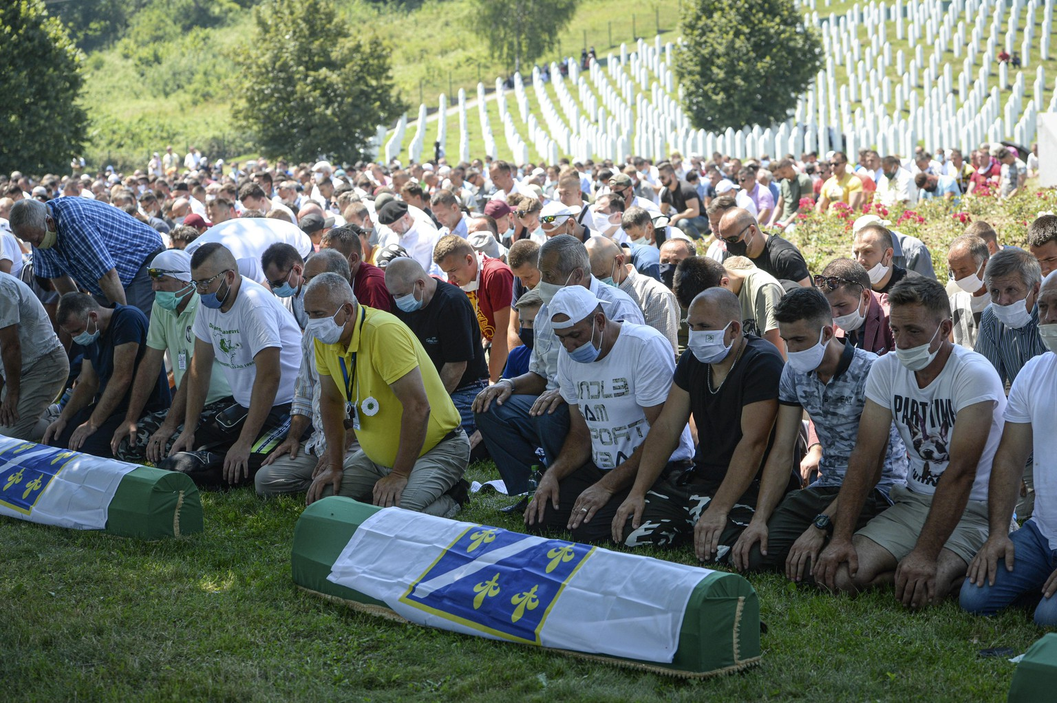 Bosnians pray by the coffins of nine massacre victims in Potocari, near Srebrenica, Bosnia, Saturday, July 11, 2020. Mourners converged on the eastern Bosnian town of Srebrenica for the 25th anniversary of the country's worst carnage during the 1992-95 war and the only crime in Europe since World War II that has been declared a genocide. (AP Photo/Kemal Softic)