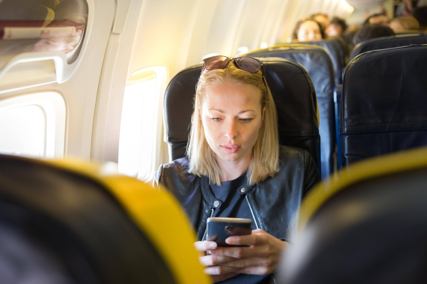 Woman using mobile phone as entertainment on airplane during commercial flight. ,model released, Symbolfoto PUBLICATIONxINxGERxSUIxAUTxONLY Copyright: xkastox Panthermedia25798726