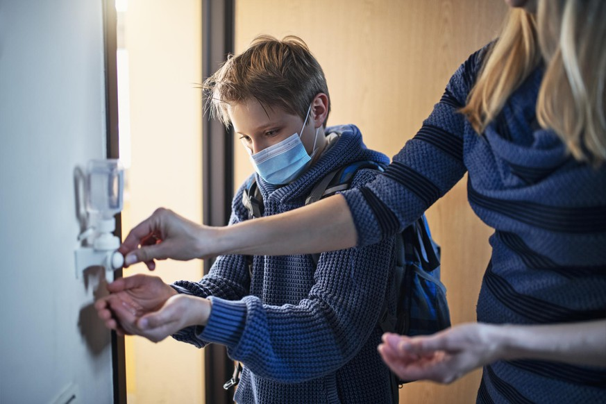 Little boy has returned from school during COVID-19 pandemic and is disinfecting his hands. The boy is wearing a surgical mask and his mother is helping him. Nikon D850