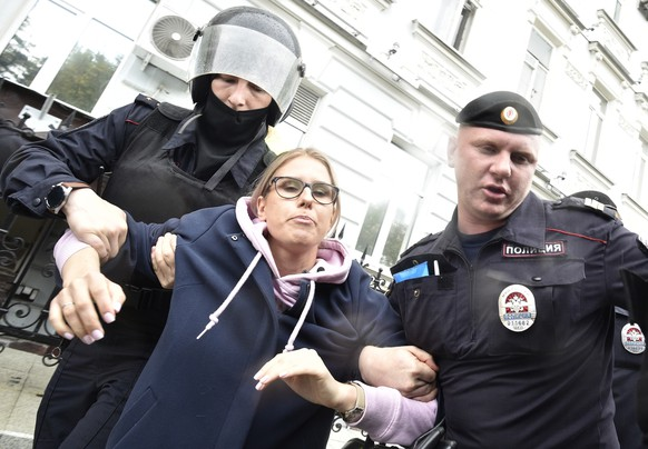 Police officers detain an opposition candidate and lawyer at the Foundation for Fighting Corruption Lyubov Sobol in the center of Moscow, Russia, Saturday, Aug. 3, 2019. (AP Photo/Dmitry Serebryakov)