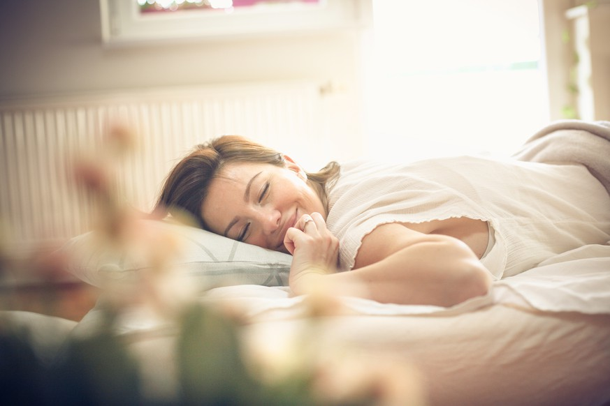 Young woman waking up in bed. Space for copy.