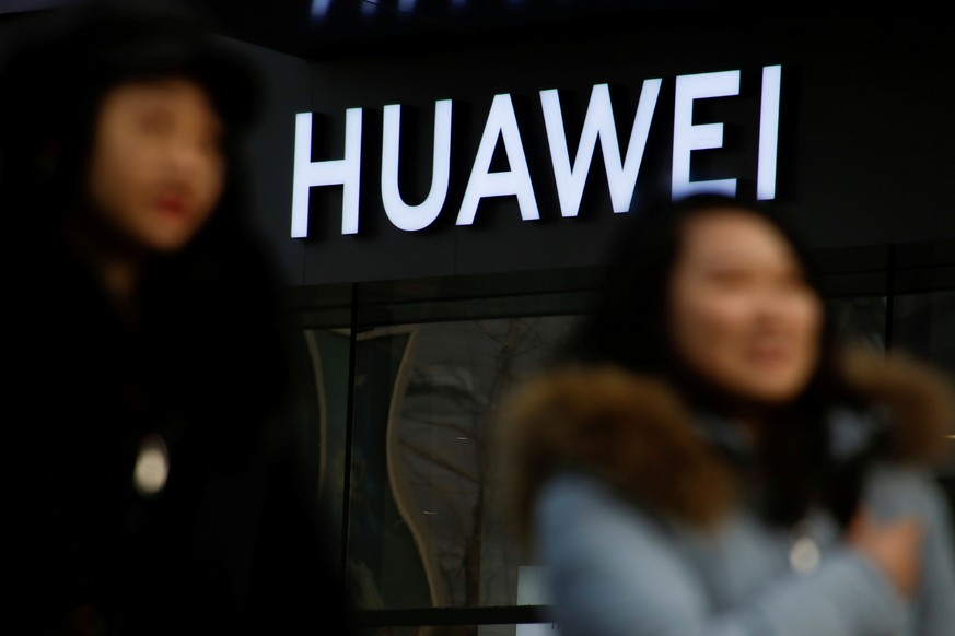 FILE PHOTO: People walk past a Huawei shop in Beijing, China, January 29, 2019. To match Special Report HUAWEI-USA/CAMPAIGN REUTERS/Thomas Peter/File Photo