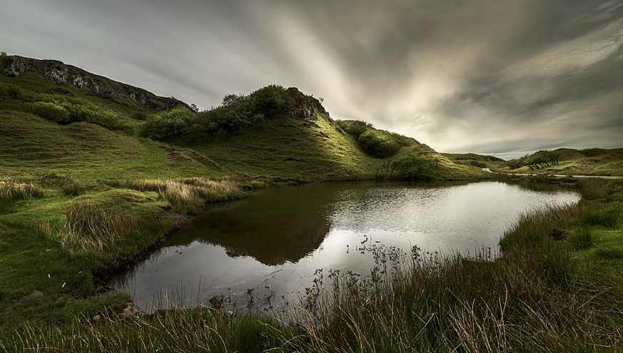 Small lagoon surrounded by grass under twilight in Fairy Glen, Sky Island, Scottish Highlands