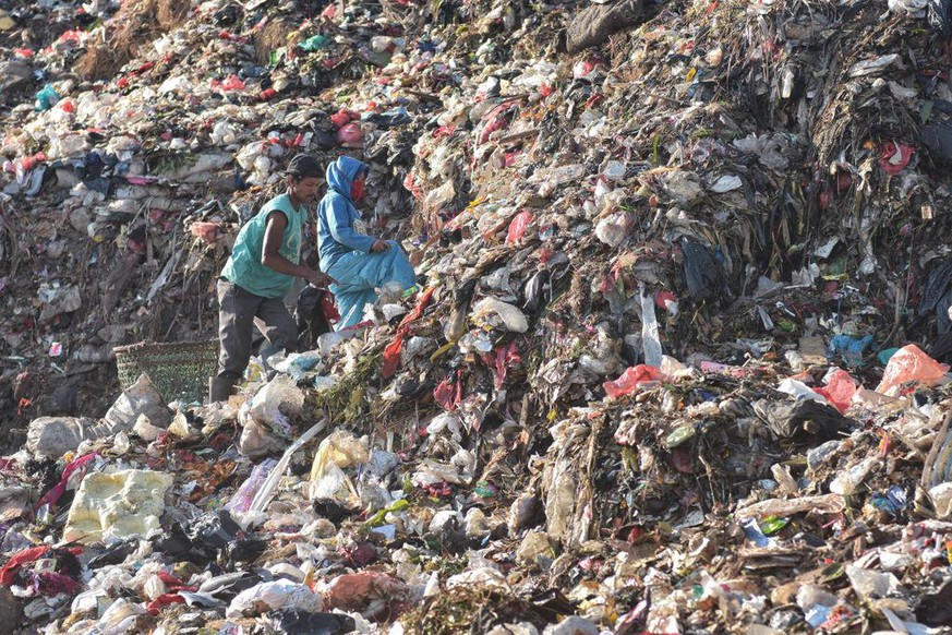 BEKASI, WEST JAVA, INDONESIA - 2019/09/11: Scavengers sort and collect plastics for recycling at the garbage mountain in Bantar Gebang landfill that is considered to be the worlds largest dump.  Jakartas Bantar Gebang Integrated Waste Treatment Area (TPST Bantar Gebang) was established in 1985. On average, 7,000 tons of waste are dumped annually at the landfill, which is expected to exceed its limit in 2021. (Photo by Agung Fatma Putra/SOPA Images/LightRocket via Getty Images)