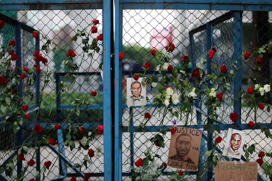 Pictures depicting George Floyd, who died in Minneapolis police custody, are seen next to messages, and flowers as a symbol of a protest against his killing, outside the U.S embassy in Mexico City Mexico May 30, 2020. REUTERS/Carlos Jasso
