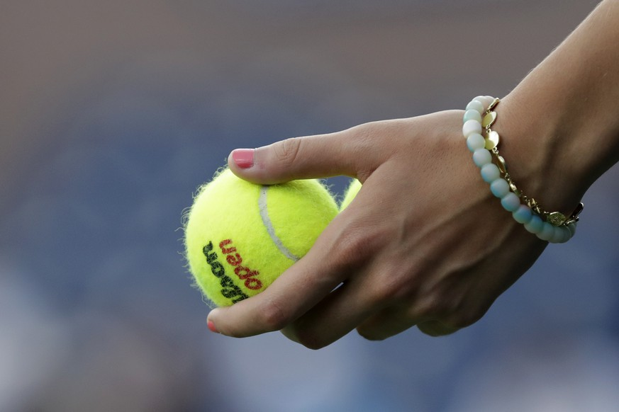 A ball girl holds tennis balls during the match between Dominik Koepfer, of Germany, and Nikoloz Basilashvili, of Georgia, during the third round of the U.S. Open tennis tournament Friday, Aug. 30, 2019, in New York. (AP Photo/Adam Hunger)