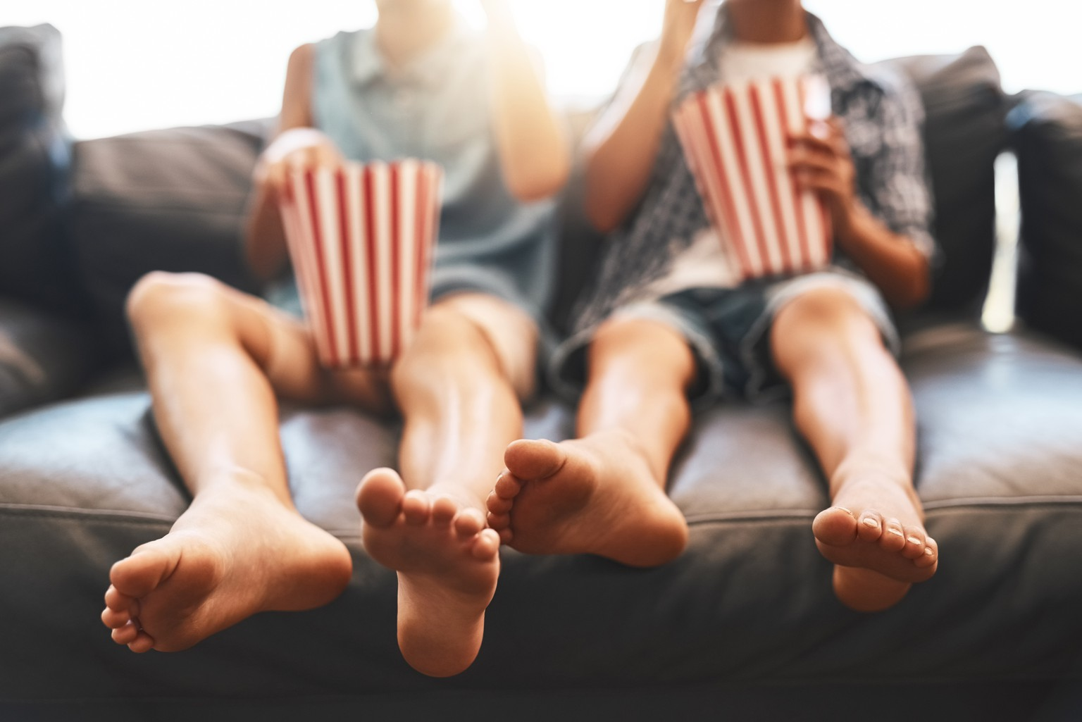 Cropped shot of a brother and sister eating popcorn and watching movies on the sofa at home