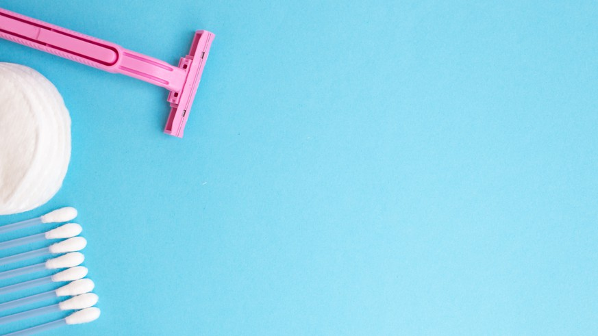 top view personal care products. white bottle, pink razor, ear sticks, cotton pads, toothbrush on blue background. copy space