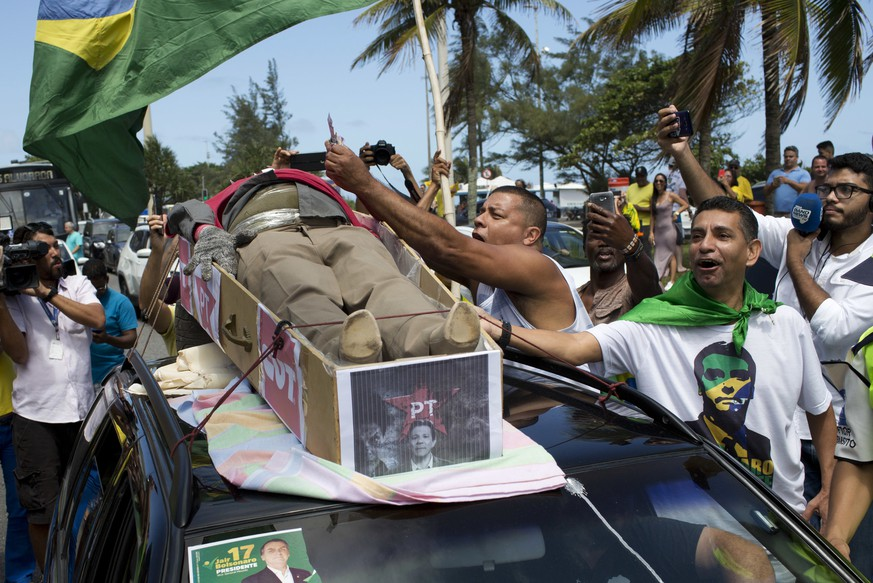 Supporters of Jair Bolsonaro, presidential candidate with the Social Liberal Party, protest with a dummy coffin symbolizing the death of the Worker's Party during the presidential runoff election, in Rio de Janeiro, Brazil, Sunday, Oct. 28, 2018. Bolsonaro is running against leftist candidate Fernando Haddad of the Workers' Party. (AP Photo/Silvia Izquierdo)