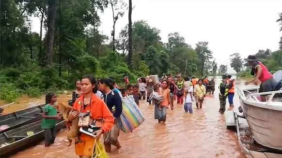 People walk through flooded area after being brought to safety by boat in Sanam Xay district, Attapeu Province, Laos after a hydropower dam under construction in Southern Laos collapsed, in this still picture taken from social media video obtained July 24, 2018.  ATTAPEU TODAY/ via REUTERS  ATTENTION EDITORS - THIS IMAGE HAS BEEN SUPPLIED BY A THIRD PARTY. MANDATORY CREDIT. NO RESALES. NO ARCHIVES. MUST ON SCREEN COURTESY: ATTAPEU TODAY.