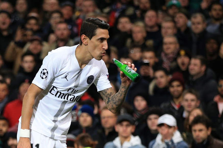 MANCHESTER, ENGLAND - FEBRUARY 12:  Angel Di Maria of Paris Saint-Germain makes to drink from a bottle of beer thrown onto the pitch during the UEFA Champions League Round of 16 First Leg match between Manchester United and Paris Saint-Germain at Old Trafford on February 12, 2019 in Manchester, England. (Photo by Marc Atkins/Getty Images)
