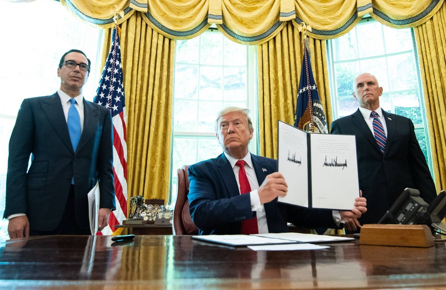 President Donald Trump, joined by Treasury Secretary Steven Mnuchin (L) and Vice President Mike Pence, holds up a copy of an executive order for additional sanctions against Iran and its leadership, after signing it in the Oval Office at the White House in Washington D.C. on June 24, 2019. The sanctions come in the wake of rising tensions in the Middle East including Iran s recent shooting down of a U.S. drone. PUBLICATIONxINxGERxSUIxAUTxHUNxONLY WAP20190624317 KEVINxDIETSCH
