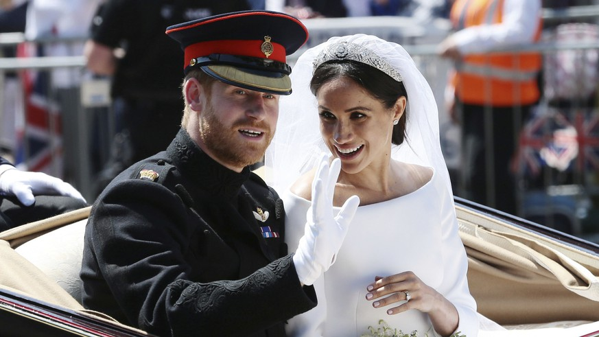 Britain's Prince Harry and Meghan Markle ride in an open-topped carriage after their wedding ceremony at St. George's Chapel in Windsor Castle in Windsor, near London, England, Saturday, May 19, 2018. (Aaron Chown/pool photo via AP) |