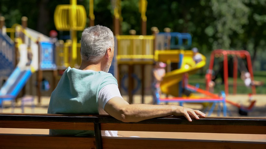 Male pensioner sitting on bench and watching grandkids on playground, family