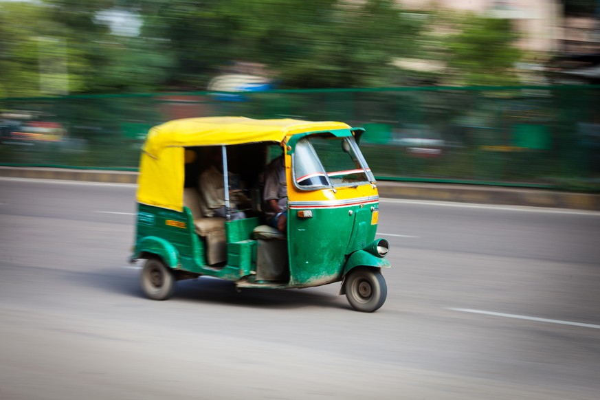 Indian auto (autorickshaw) taxi in the street. Motion blur. Delhi, India