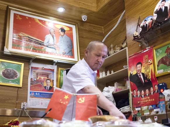 Xinjiang Uyghur Autonomous Region Photo taken on July 4, 2018, shows a man at a restaurant decorated with pictures of Chinese government leaders in Urumqi in the country s Xinjiang Uyghur Autonomous Region. PUBLICATIONxINxGERxSUIxAUTxHUNxONLY