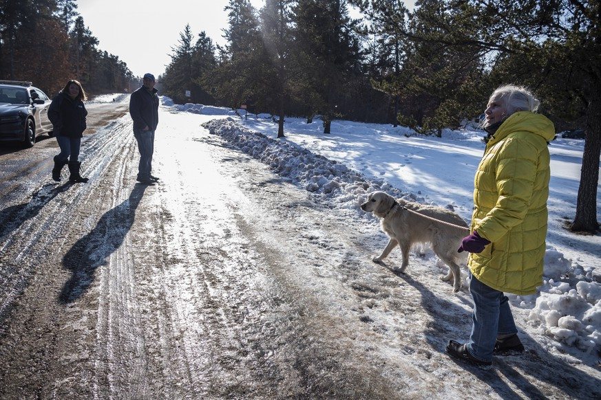 Kristin Kasinskas, left, husband, Peter, and Jeanne Nutter and her dog Henry head back to their homes after speaking with the media Friday, Jan. 11, 2019, in Gordon, Wis. Kristin Kasinskas called 911 on Thursday, to report that Jayme Closs, 13, had been found after Nutter, who was out walking her dog, encountered her and brought her to Kasinskas' house. Closs went missing in October after her parents were killed. (Richard Tsong-Taatarii/Star Tribune via AP)