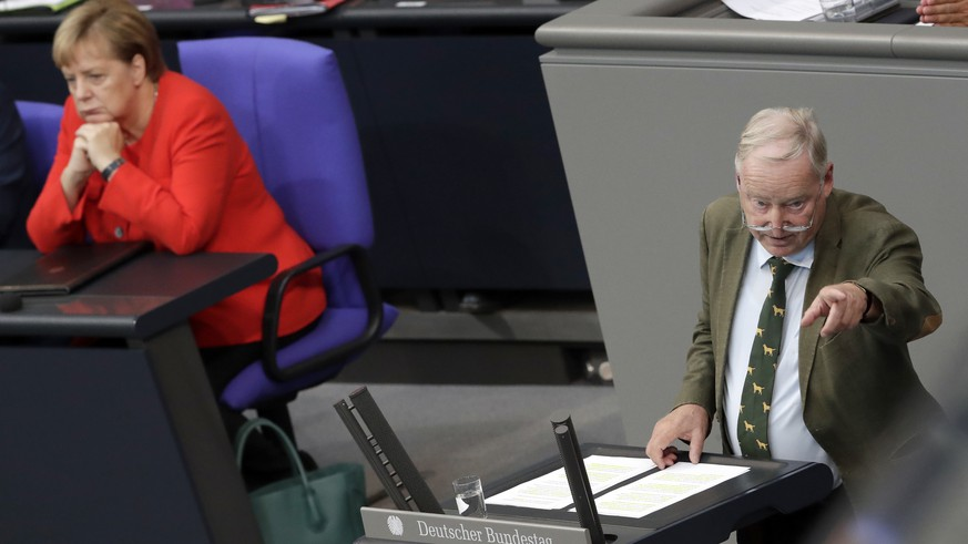 German Chancellor Angela Merkel, left, attends the speech of Alexander Gauland, co-faction leader of the Alternative for Germany party, right, during a budget debate as part of a meeting of the German federal parliament, Bundestag, at the Reichstag building in Berlin, Germany, Wednesday, Sept. 12, 2018. (AP Photo/Michael Sohn)